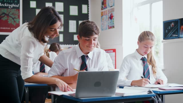 vidéos et rushes de enseignante, aider les élèves à l'aide d'ordinateur dans la salle de classe - uniforme