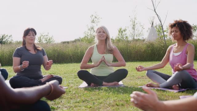 insegnante leader gruppo di uomini e donne maturi in classe al ritiro yoga all'aperto - donne mature video stock e b–roll