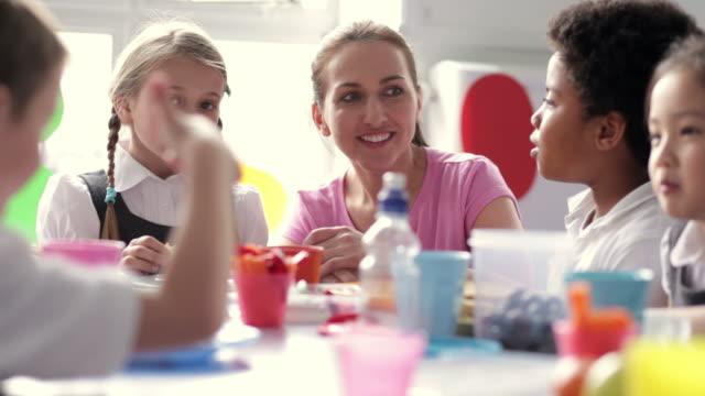 Hembra maestro supervisando a los niños comiendo comida escolar - vídeo