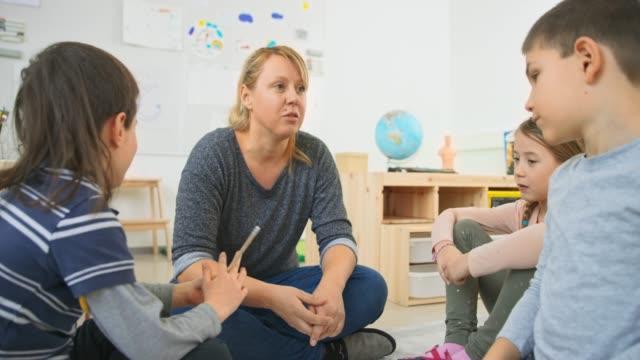 vídeos de stock, filmes e b-roll de professor fêmea que fala às crianças enquanto sentam-se em um círculo na sala de aula - professor de pré escola