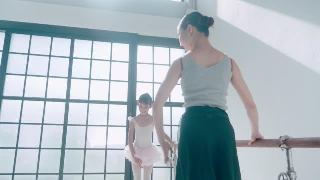 Female teacher teaches little girl in ballet school stock video