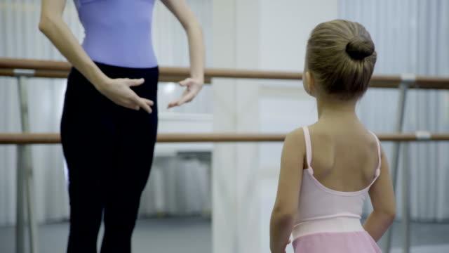 weibliche lehrer lehrt kleines mädchen in der ballettschule - ballettschuh stock-videos und b-roll-filmmaterial
