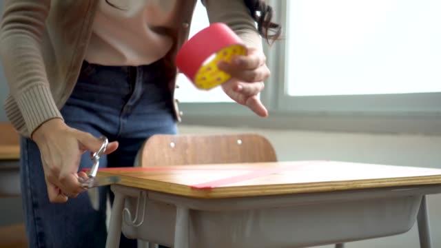 insegnante di sesso femminile che usa una burocrazia sui banchi della scuola primaria per mantenere la politica di misure di distanziamento sociale nella costruzione dell'istruzione per covid19 nuovo concetto normale - didattica a distanza video stock e b–roll