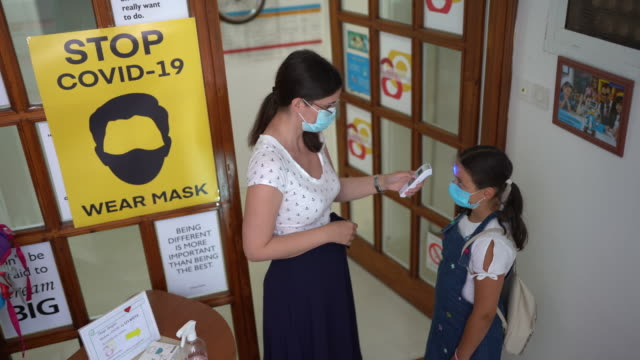 Female teacher using thermometer temperature screening for girl student
