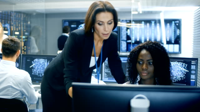 Female Team Leader Consults Young Neural Network Architect. They Work in a Crowded Office on a Neural Network/ Artificial Intelligence Project. Office Space Has Data Server. video