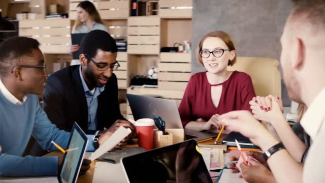 kvinnliga ledare ger anvisningar till kollegor. friska multietniskt teamet diskuterar business marketing strategi. 4k - kulturer bildbanksvideor och videomaterial från bakom kulisserna