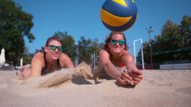 Zeitlupe: Beide weiblichen Teamkollegen Tauchen für Ball während ein Beach-Volleyball-Spiel. – Video