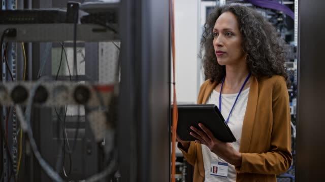 female technician doing a checkup in the server room - supporto tecnico video stock e b–roll