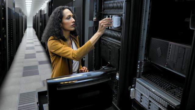 LD Female technician inserting hard discs in the server room