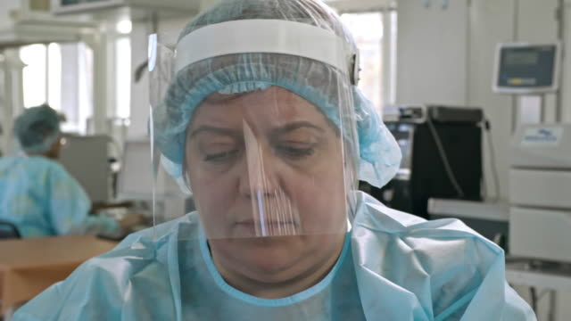 Female Technician Working in Blood Drawing Lab Closeup of mid-aged female technician in medical face shield and uniform working in laboratory shield stock videos & royalty-free footage