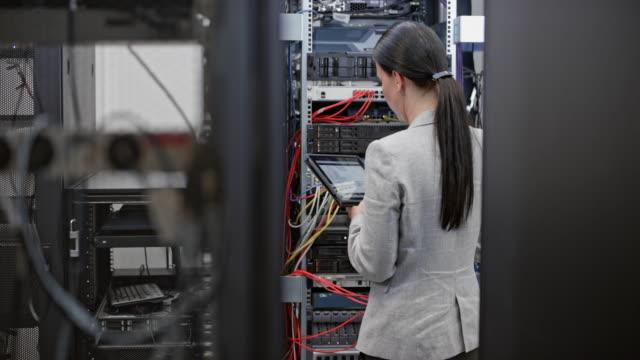 ds-weiblich-techniker arbeiten im serverraum - it support stock-videos und b-roll-filmmaterial