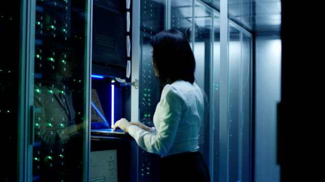 kvinnliga tekniker arbetar på en bärbar dator i ett datacenter - server room bildbanksvideor och videomaterial från bakom kulisserna