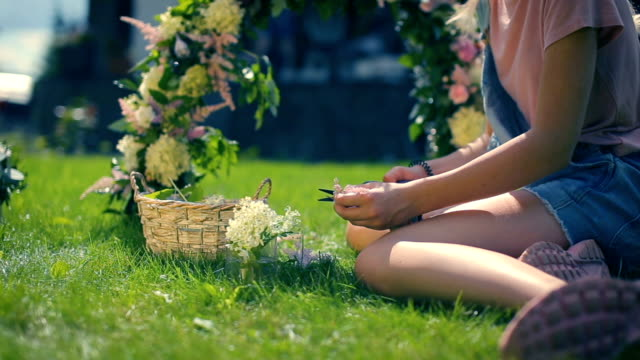 female teen girl enjoying flowers decorations in the green grassy sunny summer garden video