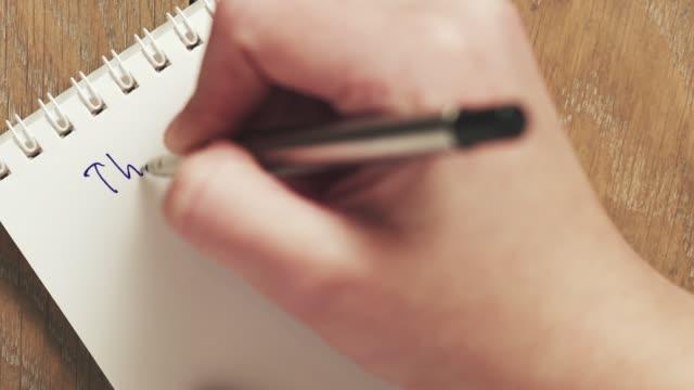 adolescente femmina scrive cose da fare sul blocco note vuoto - to do list video stock e b–roll