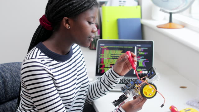 Female Teenage Pupil Building Robot Car In Science Lesson