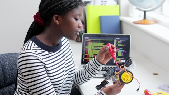 bilim dersinde kadın genç öğrenci bina robot araba - kızlar stok videoları ve detay görüntü çekimi