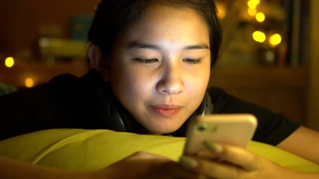 夜の寝室でスマート フォンを使う女性のティーンエイ ジャーの女の子 - スマホ ベッド点の映像素材/bロール