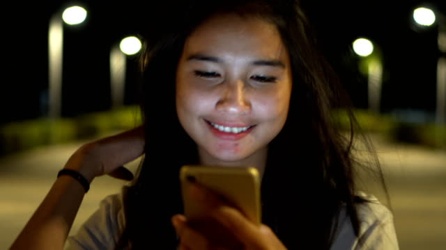 female teenager girl using smartphone while walking in the park at night video