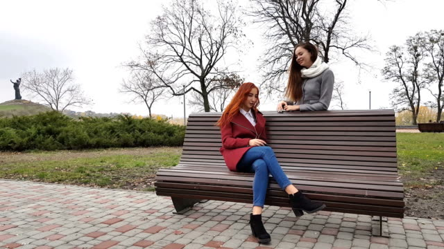 Female teenagers listening to music on smartphone at the bench in an autumn city park video