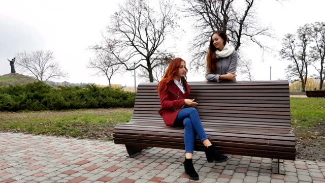 Female teenagers listening to music on smartphone at the bench video
