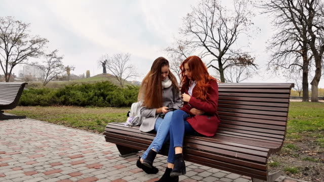 Female teenagers listening to music on smartphone sitting on the bench video