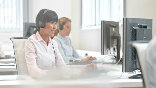 DS Female telephone operator talking at her desk Medium dolly shot of an Asian woman in light pink shirt with her headphones on her head talking to the customer over the phone. call centre videos stock videos & royalty-free footage