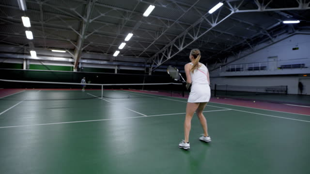Female tennis player playing on indoor court against male player video