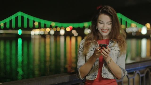 Weibliche Benachrichtigungen und SMS auf Handy in der Stadt bei Nacht – Video