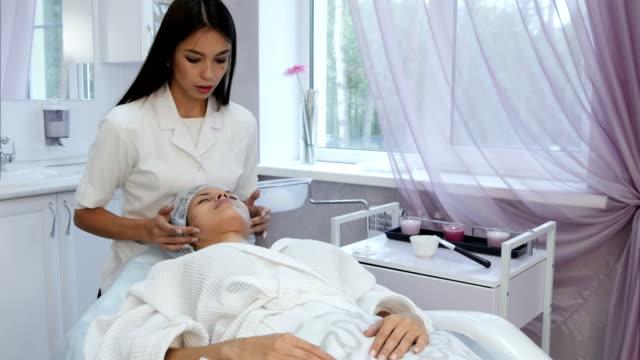 female therapist doing professional rejuvenating face massage - prendersi cura del corpo video stock e b–roll