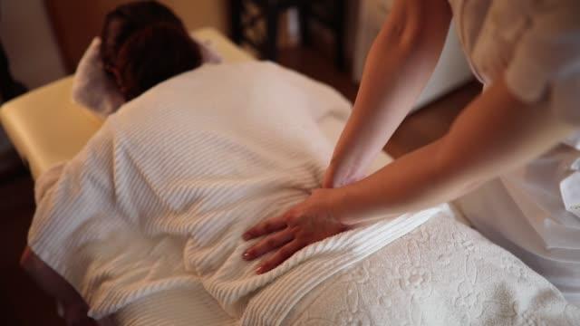 Terapeuta femenina dando masaje en salón privado - vídeo