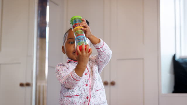 female toddler in nursery at home playing with plastic toy - giocattolo video stock e b–roll