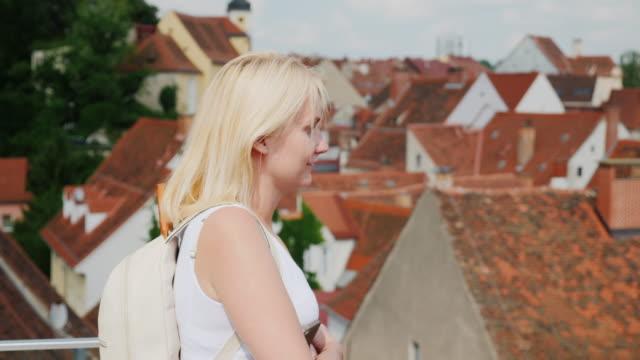 bir kadın turist eski eupropean kentin çatıları hayran. avrupa'nın turizm - styria stok videoları ve detay görüntü çekimi