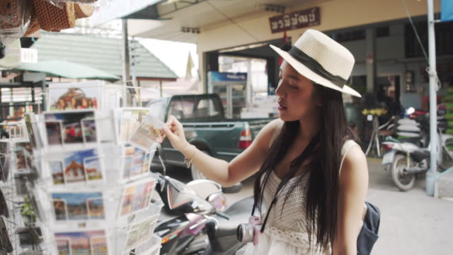 Female tourist choose and picking post card Young Asian Female tourist choose and picking post card and smiling souvenir stock videos & royalty-free footage