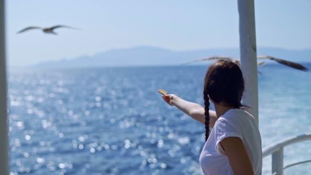 Female tourist feeding seagulls