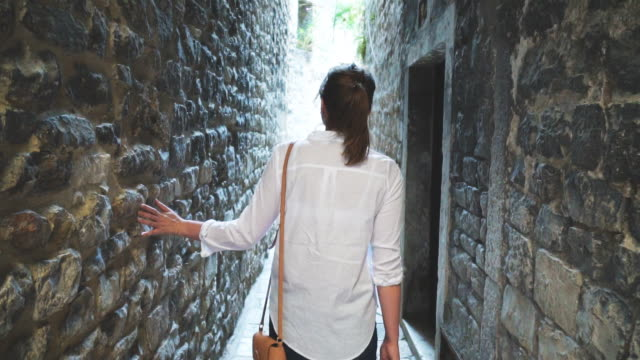 female tourist is walking along the old narrow streets of the city. - хорватия стоковые видео и кадры b-roll