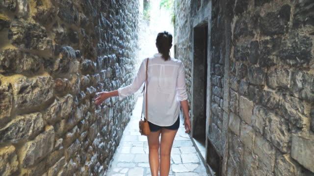 kvinnlig turist promenader längs de gamla smala gatorna i staden. - stenhus bildbanksvideor och videomaterial från bakom kulisserna