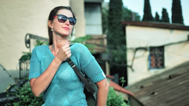 female tourist pulling up heavy backpack on one shoulder smiling having vacation - viaggiare zaino in spalla video stock e b–roll