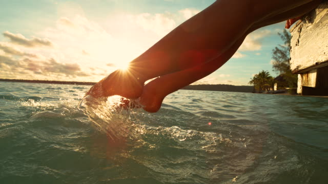 close up: female tourist splashing water with her bare feet on a sunny morning. - caraibi video stock e b–roll