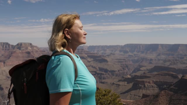 Female Tourist Stands At The Top Of Grand Canyon Inhaling Clean Fresh Air Female hiker with backpack at the top of Grand Canyon, enjoying the view and success, slowly breathe the clean desert air full breasts, closes her eyes with pleasure and exhales. Slow motion canyon stock videos & royalty-free footage