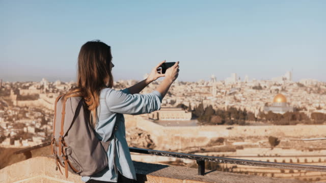 Female tourist takes photos of Jerusalem old town. Pretty Caucasian traveler woman smiling with backpack. Israel. 4K video