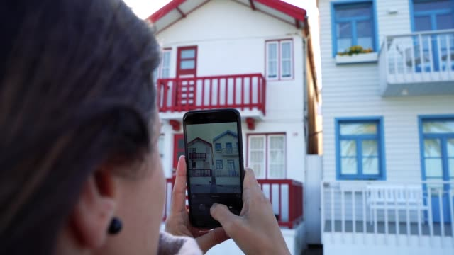 vídeos de stock e filmes b-roll de female tourist taking pictures at the city aveiro in portugal. famous beach for the striped colorful houses. - aveiro