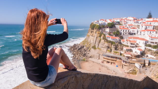 Female tourist taking pictures of village on cliffs by ocean video