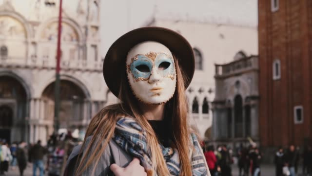 Female tourist with long hair posing in a full face traditional carnival mask standing at Venice city square slow motion Female tourist with long hair posing in a full face traditional carnival mask standing at Venice square slow motion. Stylish fashionable local woman enjoying atmosphere of famous Venetian carnival. mask disguise stock videos & royalty-free footage