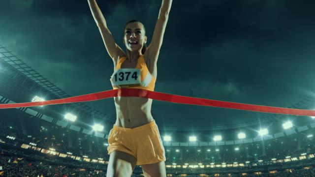 vídeos y material grabado en eventos de stock de femenino de pista y campo runner atraviesa alcanzar la línea de meta - meta