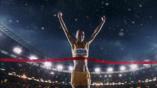 kadın atletizm runner geçerek bitiş çizgisine - başarı stok videoları ve detay görüntü çekimi