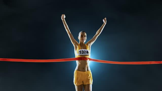 vídeos y material grabado en eventos de stock de atletismo femenino corredor cruza la línea de llegada - meta