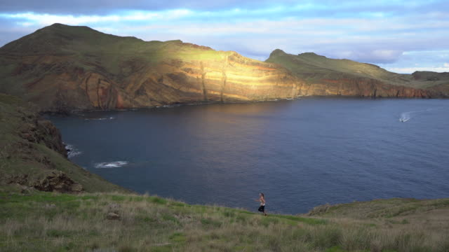 Female trail runner ascending hill overlooking Madeira coastline