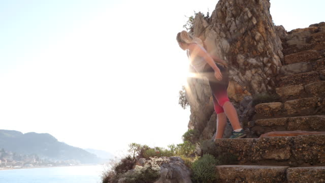 female trail runner ascends stone steps at sunrise - pantaloni capri video stock e b–roll