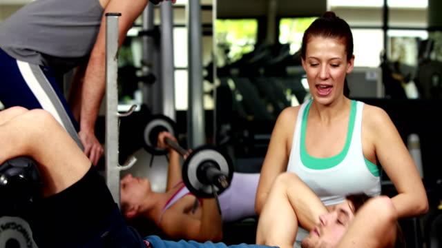 женский тренер, помогая человек делает его скручивания - спортивный бюстгальтер стоковые видео и кадры b-roll
