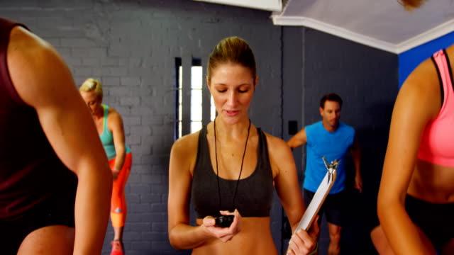 vidéos et rushes de formateur femme regardant chronomètre alors que les gens exerçant - chrono sport